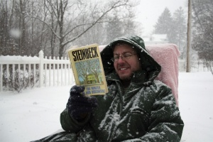 "Man reading John Steinbeck's ""The Winter of Our Discontent"" in the snow."