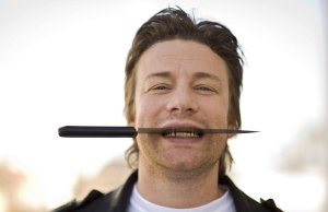Jamie Oliver holding a knife between his teeth
